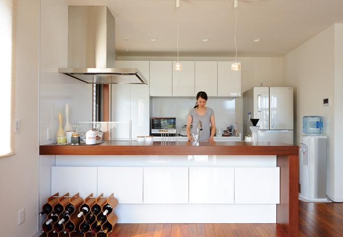 かなめ創建【デザイン住宅、省エネ、間取り】キッチン:壁に合わせて白で統一したデザイン性豊かなシステムキッチン。背面の食器棚はもちろん、カウンターの下にも豊富な収納スペースを持ち、使い勝手も抜群