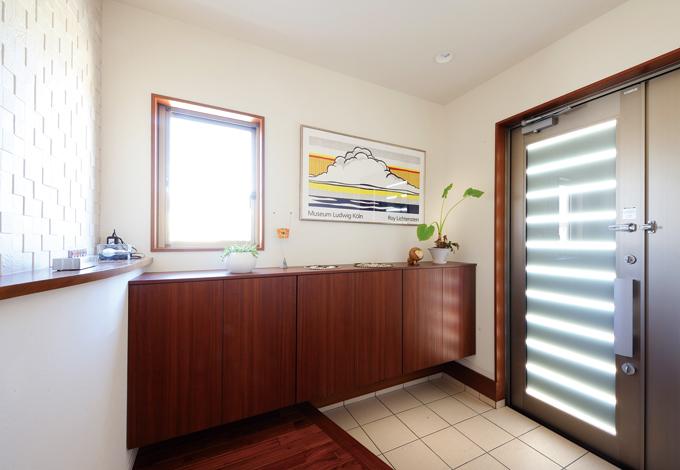 かなめ創建【デザイン住宅、省エネ、間取り】効果的に光を採り込む玄関。照明や絵画もおしゃれ