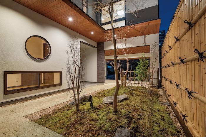 アイワホームサービス【デザイン住宅、高級住宅、ガレージ】エントランスから続く庭。街中にいながら旅館に来たような非日常の空間で心に安らぎをもたらす。和風建築で見られる地窓を巧みに取り入れることで通風にも配慮