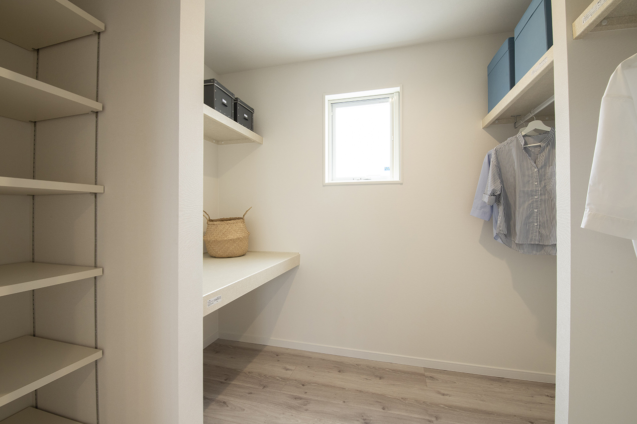 遠鉄ホーム【磐田市・モデルハウス】主寝室に併設されたウォークインクローゼット。向かって左右に収納棚を設けても、姿見を置けるスペースを確保