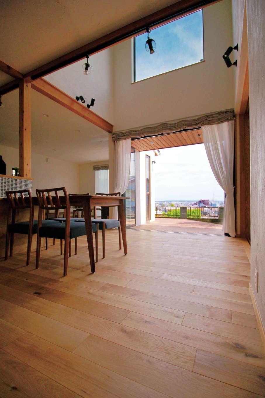 アイジースタイルハウス【デザイン住宅、自然素材、省エネ】フルオープンの窓を開けると、デッキ、庭とひとつながりになるダイニング。吹抜けの高窓からたっぷりの光が降り注ぐ。無垢のオーク材を張った床の経年変化も楽しみ