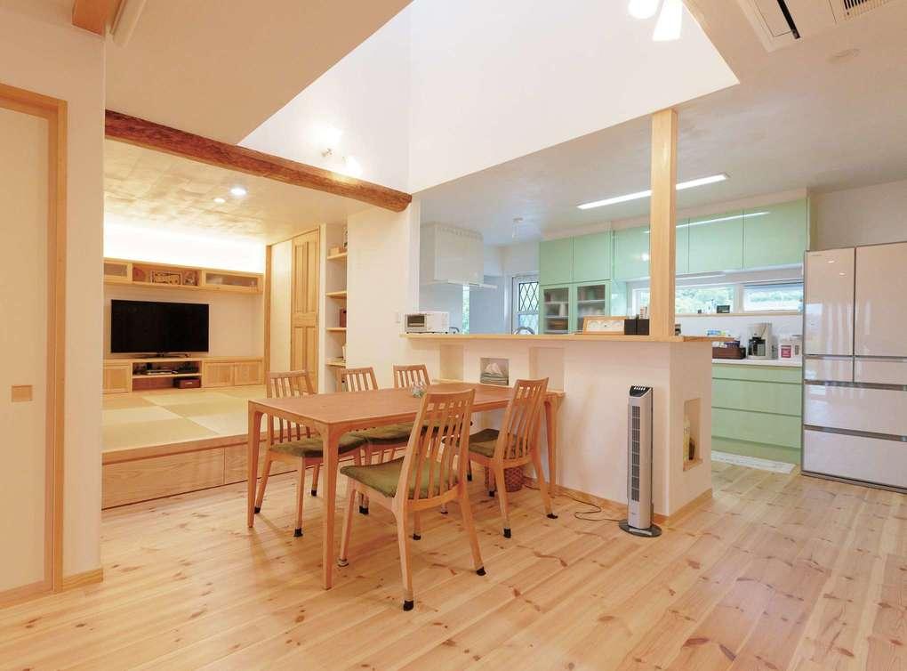 アイジースタイルハウス【二世帯住宅、自然素材、省エネ】明るさを確保するために、大きな吹抜けを採用した。子世帯と比べ家具の色合いを抑え、ライムグリーンのキッチンを空間の差し色に