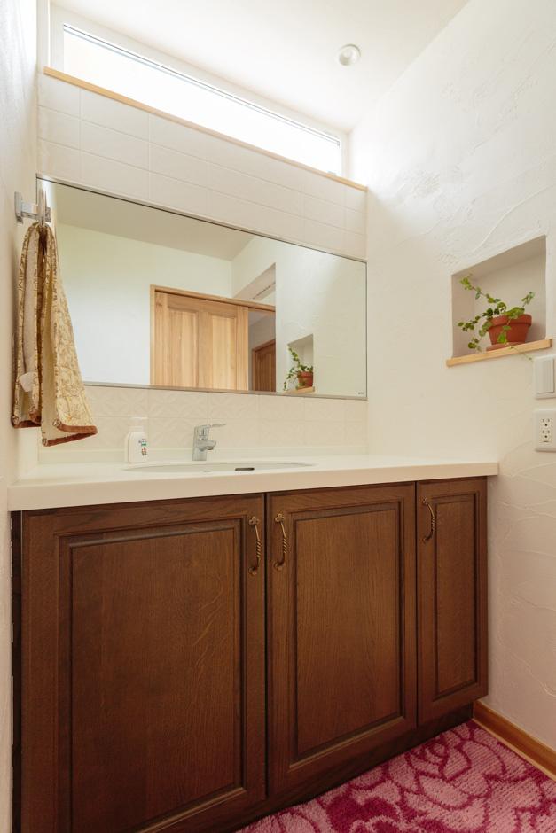 アイジースタイルハウス【収納力、自然素材、間取り】ハイサイドライトで採光たっぷりの洗面室は、気持ちよい朝を迎えられそう。色の統一感があり、清潔感のあるカラースキームも魅力。上品な花柄の白いタイルは奥さまが見学会でひと目惚れしたアイテムで、使うのがもったいないほど気に入っている