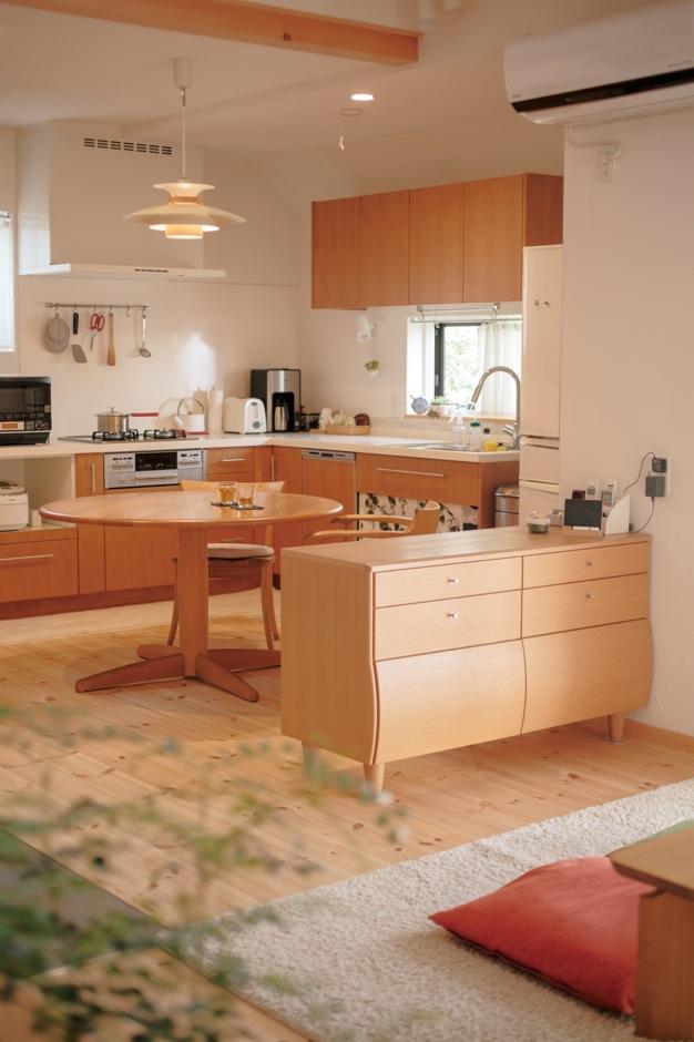アイジースタイルハウス【デザイン住宅、自然素材、省エネ】空間を広く使うために、キッチンはL字型を採用。窓からジューンベリーの木を見ながら楽しく料理できる。ローボードでリビングと緩やかにゾーニングした