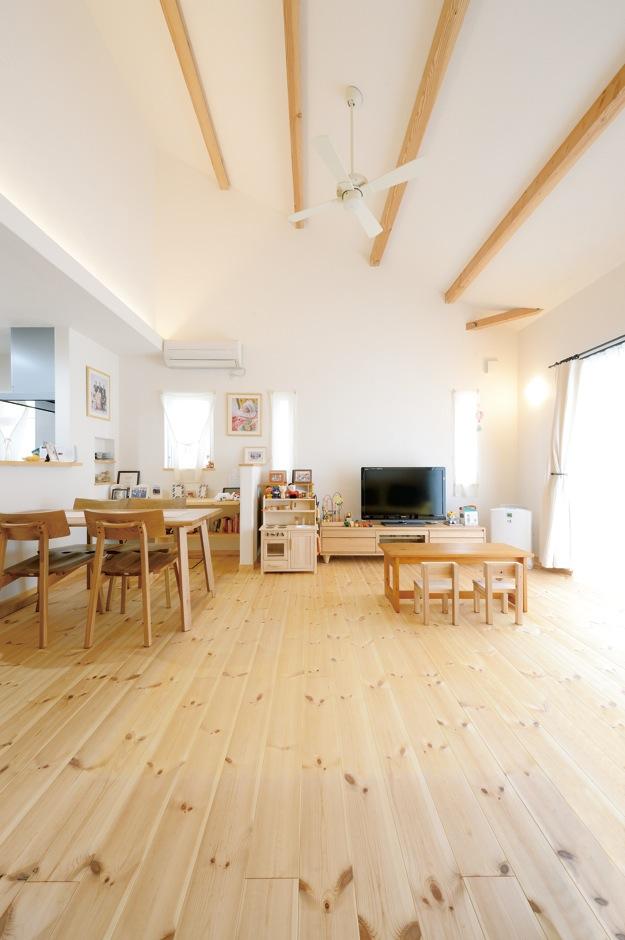 アイジースタイルハウス【収納力、自然素材、間取り】大胆な勾配天井を採用したリビングは吹抜けのような開放感がある。漆喰の白い空間に現しの木がアクセントになっている。無垢の床の経年変化も楽しみ