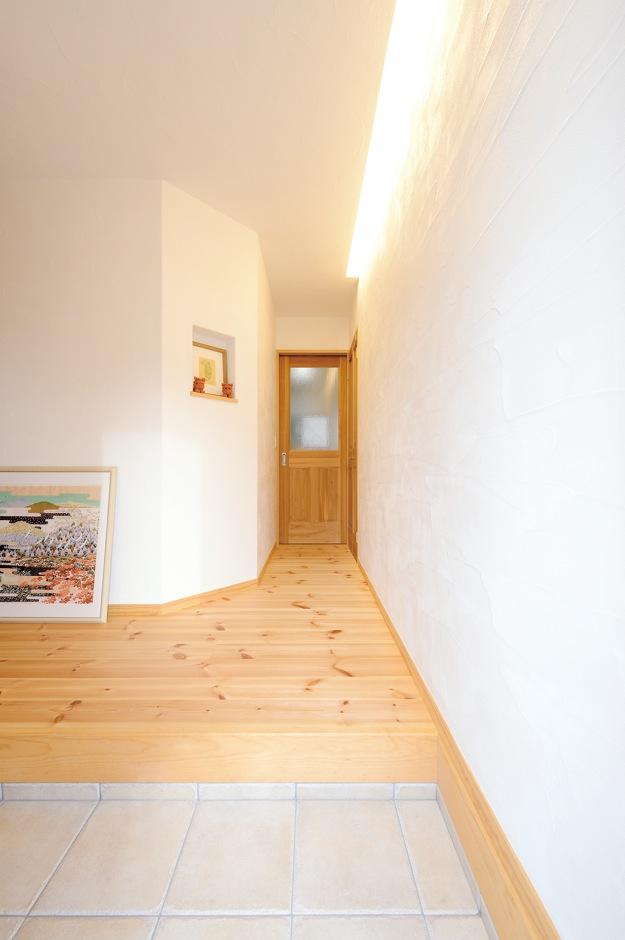 アイジースタイルハウス【収納力、自然素材、間取り】入った瞬間、木のやさしい香りに包まれる玄関ホール。白い壁面をギャラリーとして使うため、間接照明が当たるように設計した