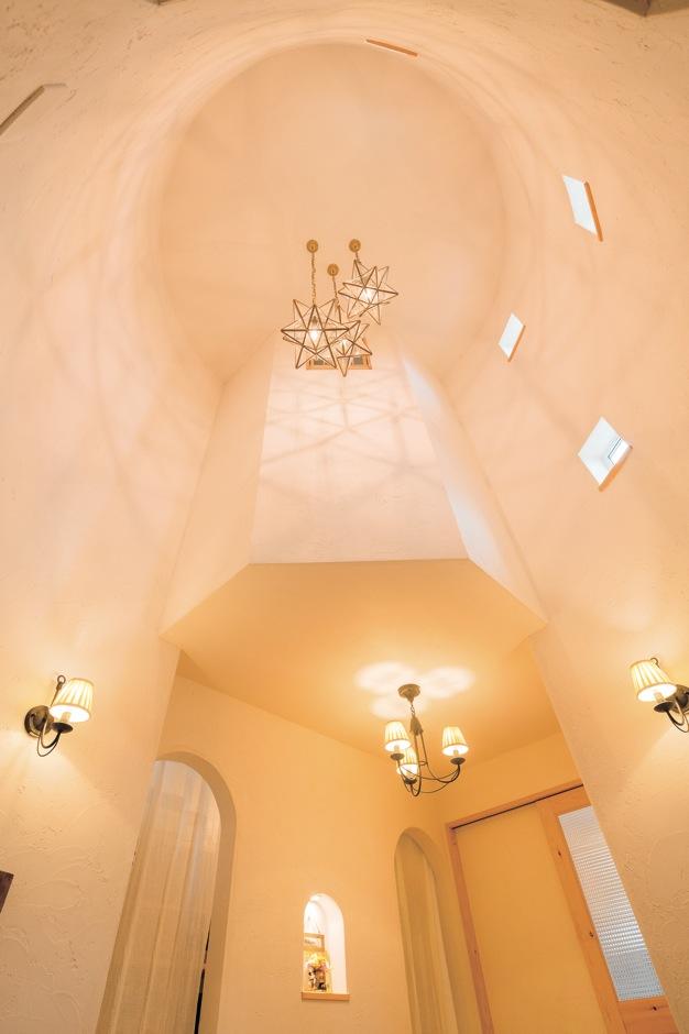 アイジースタイルハウス【子育て、輸入住宅、自然素材】塔の内部にあたる玄関ホール。丸い筒のような高天井の空間に、小さな窓からやさしく陽が注ぎ、照明の灯りが塗り壁の質感に豊かな表情を与えている