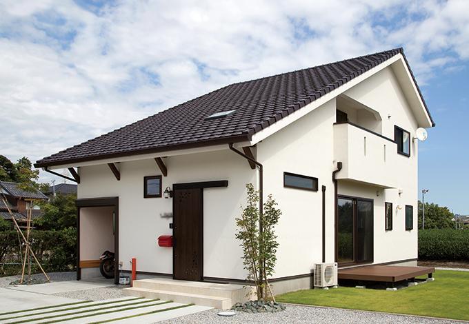 アイジースタイルハウス【自然素材、省エネ、ガレージ】インナーガレージを備えた大屋根の外観がのどかな茶畑の風景にほどよくとけこむ。玄関の天窓がアクセントにもなっている。シンボルツリーは紅葉とアオダモ