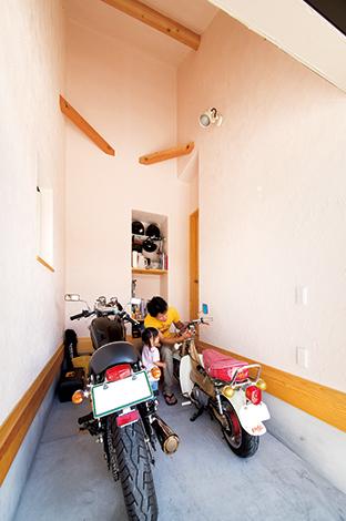 アイジースタイルハウス【自然素材、省エネ、ガレージ】ご主人の夢を叶えたビルトインガレージ。奥さまはバイクに乗らないけれど、MちゃんはHONDAのシャリーに興味津々。壁は淡いピンク色の漆喰を採用