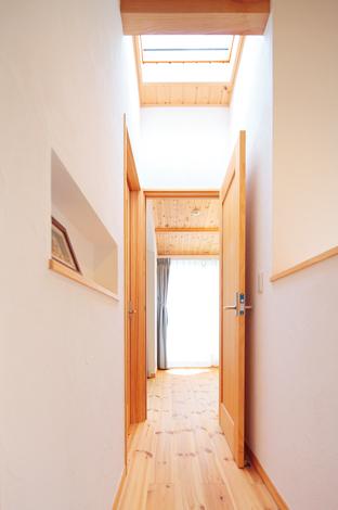 トップライトと勾配天井で廊下を明るく広く見 せている