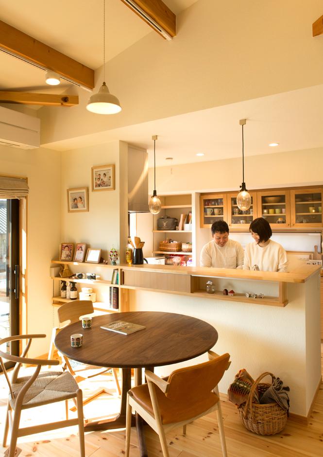 Casa(カーサ)【子育て、二世帯住宅、自然素材】リビングに面した対面式キッチンは、夫婦のお気に入りをギュッと集めた場所だ。木製カウンターに似合うカップボードや、ダイニングテーブルはインテリアショップにオーダー。照明は『カーサ』のコーディネーターが提案したもの