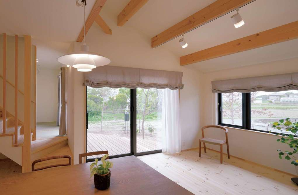 Casa(カーサ)【子育て、収納力、自然素材】勾配天井が開放感を生むリビングダイニング。大きな窓越しの庭や、リビング階段の向こうにある和室までを見渡せる