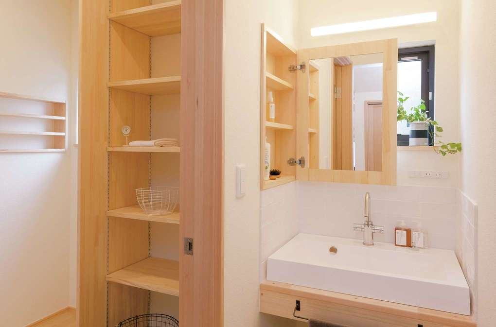 Casa(カーサ)【子育て、収納力、自然素材】洗面台は壁の収納棚の戸に鏡を設置。普段は収納しておくので、正面の窓から自然光が入る