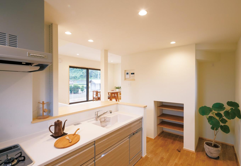Casa(カーサ)【子育て、趣味、自然素材】1段下がったキッチン内部からはリビングを一望できる。ニッチ収納や階段下収納も豊富に用意さ れ、家事がしやすいと奥さまも大満足