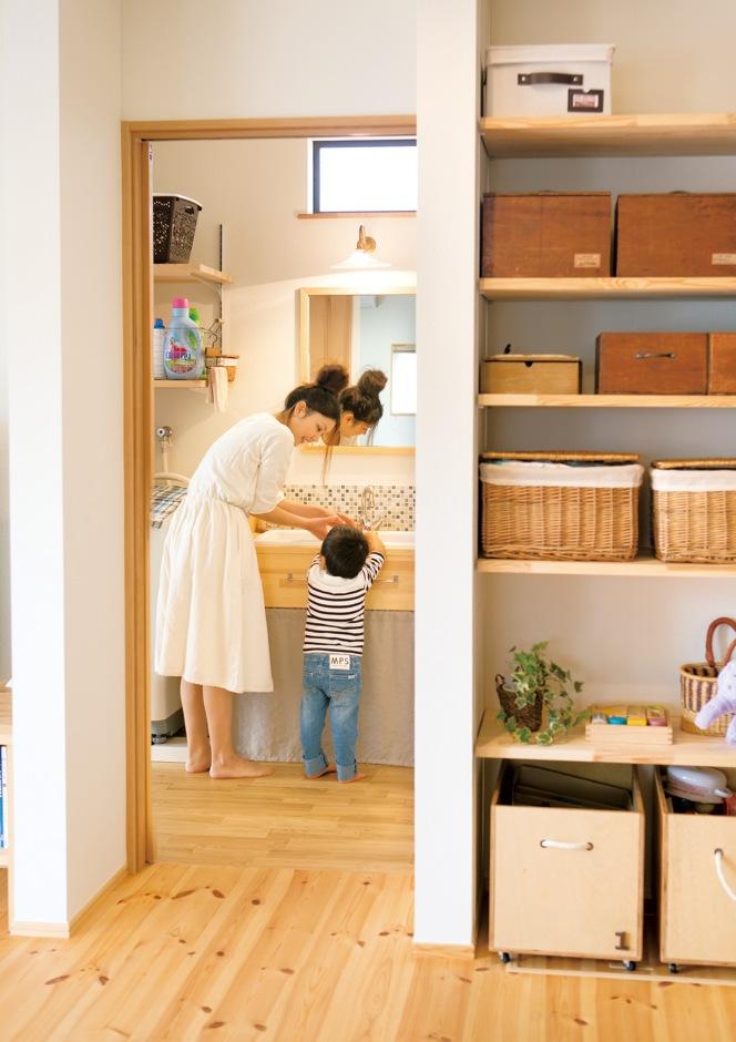 Casa(カーサ)【子育て、趣味、自然素材】ナチュラルな木製の洗面台に、夫婦が自分たちの手で貼ったモザイクタイルが映える。手前のLDKの壁面にある造作収納には、お手製の収納ボックスがずらり
