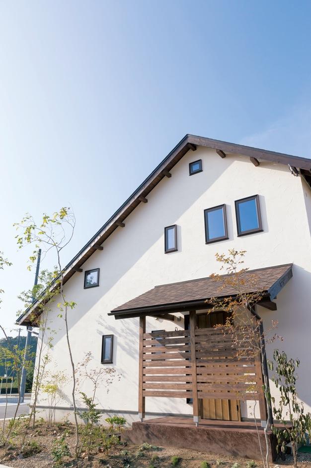 Casa(カーサ)【子育て、趣味、自然素材】大きな屋根と、漆喰の塗り壁が印象的な外観。玄関周りの植栽や外構まで『カーサ』が手がけ、統一感あるたたずまいに