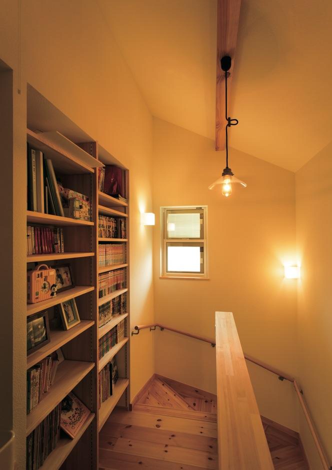 Casa(カーサ)【子育て、趣味、自然素材】階段を上がると、蔵書がずらりと並ぶ造作書棚がお出迎え。ここにまとめることで本がスッキリと収まる