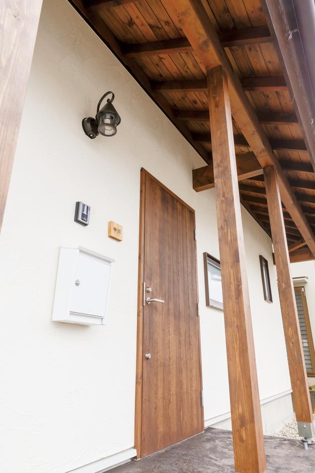 Casa(カーサ)【デザイン住宅、収納力、狭小住宅】木製ドアは奥さまの希望であずき色のポーチとも相性がいい