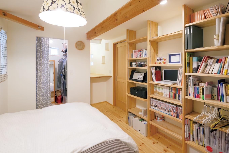 Casa(カーサ)【デザイン住宅、収納力、狭小住宅】天井まである本棚に憧れ、寝室に造作された。ウォークインクローゼットは布で目隠しをして出入りを楽に。奥の棚を上がると小屋裏収納につながる
