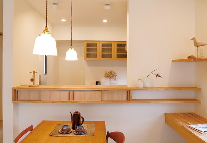 Casa(カーサ)【デザイン住宅、自然素材、省エネ】キッチンカウンターに作られた小さな収納スペースは、お箸やカトラリーなど細々したものをしまっておくのに便利。カウンター上部の吊り戸棚はなくして、開放感を演出。キッチンの裏側にパントリーも設けられた