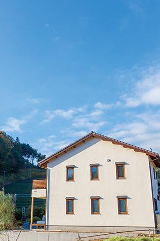Casa(カーサ)【デザイン住宅、自然素材、省エネ】自然豊かな環境にしっくり馴染んだ外観。均等に並んだ6つの木窓がコテージのよう