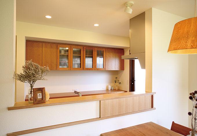 Casa(カーサ)【二世帯住宅、自然素材、間取り】母娘が一緒にキッチンに立てるよう広いスペースを確保。カウンター下の小さな引き戸が重宝している