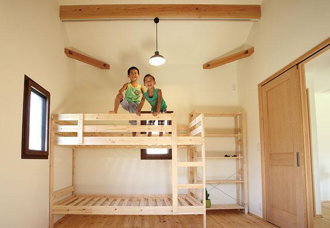 Casa(カーサ)【二世帯住宅、自然素材、間取り】勾配天井の効果で8畳とは思えない開放感。パイン のフローリングが気持ちよく、子どもたちも転がったり、裸足で駆け回ったり大はしゃぎ! ベッド、棚をナチュラルな色目で統一し、木のやさしい風合いに心が和む