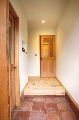 Casa(カーサ)【子育て、自然素材、間取り】こげ茶のタイルでノスタルジック風に仕上げた玄関。左手はシューズクローク