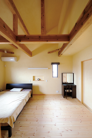 Casa(カーサ)【子育て、自然素材、省エネ】寝室:天竜杉のみごとな梁と、ほんの り色の付いたスペイン漆喰を 融合させた寝室。空気がきれ いで、以前の住まいよりも格 段に眠りが深くなったという