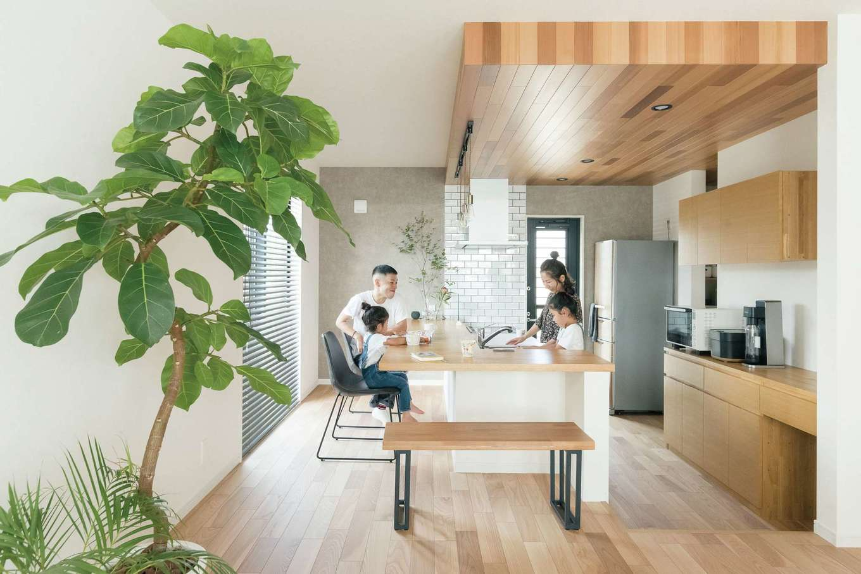 KOUBOU STYLE 建築工房相良【デザイン住宅、子育て、間取り】キッチンは家族が自然と集まるカフェみたいな空間。下がり天井を設け、リビングとゆるやかにゾーニング。幅広のカウンターは食事だけでなく、子どもたちが勉強をしたり、夫婦でお酒を飲んだり、マルチに活躍する特等席