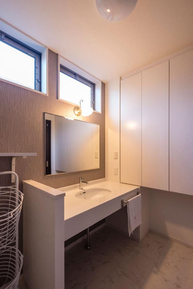 洗面脱衣所は、ホテルのようにすっきりさせたいという奥さまの希望でシンプルに。鏡は希望のサイズでオーダー。壁面には扉付きの収納を