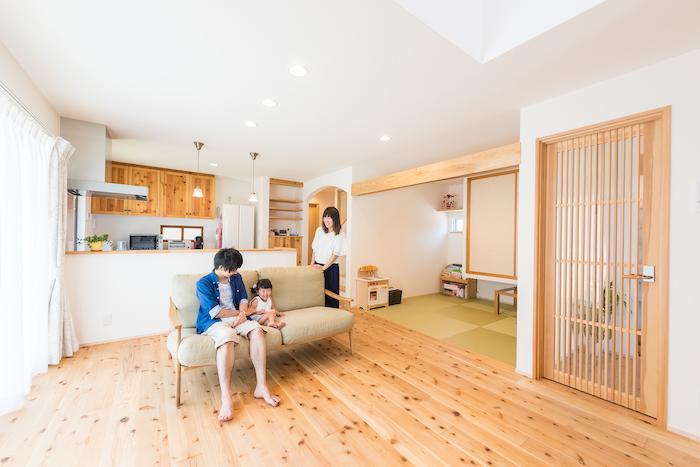 アトラス建設【子育て、自然素材、省エネ】対面式キッチンと大きな窓の明るいLDK。素足が心地良い無垢の床、やさしい質感で汚れづらい漆喰の壁など、自然素材をふんだんに使用している。設計面では「使いやすさ」とあわせて、「ちょっと可愛くしたい」という奥さまの要望をさりげなく採り入れている