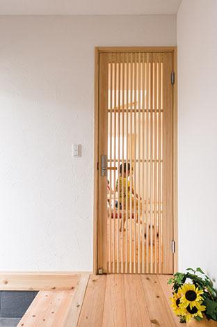 アトラス建設【子育て、和風、自然素材】LDKの気配が玄関に伝わる格子状の建具。町屋テイストを感じさせるデザインだ。ちなみにM邸の室内ドアは、「すべて無垢(桐・赤松)の建具」が使われている