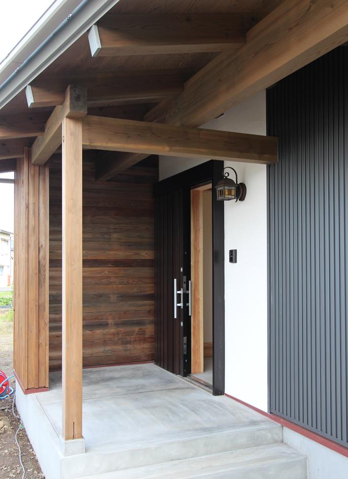 アクトホーム(木の住まいづくり研究所)【収納力、自然素材、間取り】玄関にも深い軒を。落ち着きのある木の色合いがあたたかに迎え入れてくれる