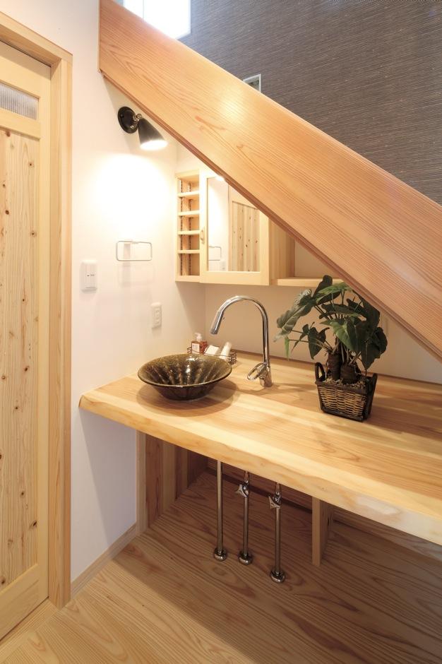 階段下を利用した洗面スペース。大井川スギのカウンターに、手水鉢には遠州七窯の1つとして知られる地元の「志戸呂焼」が使われた