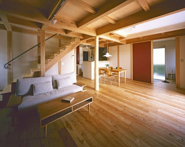 カラマツの床が清々しいリビング。大井川スギを柱・梁の骨太軸組に使用。やさしい存在感の杉丸太の大黒柱や、間仕切壁のような引戸にも注目