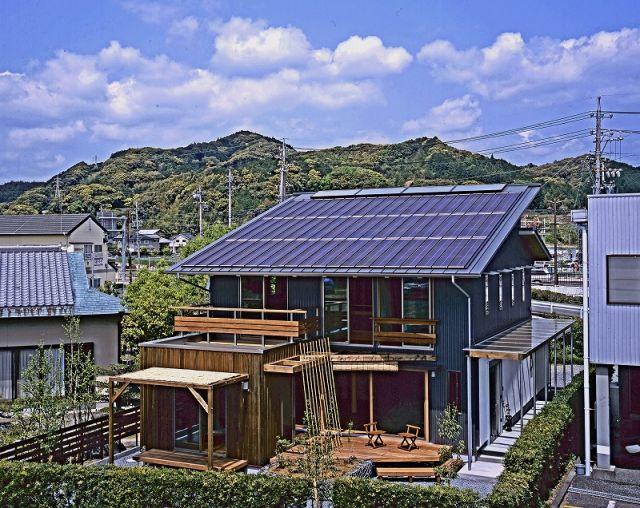 ガルバリウム鋼板とウッドサイディングのコントラストが美しい外観。屋根の上には太陽光発電パネルと太陽熱暖房のWソーラーシステム