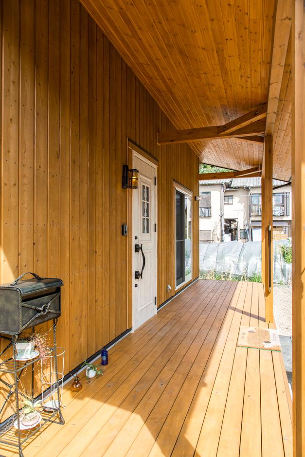 玄関前の深い軒は雨を防ぎ、家族を温かに迎えてくれる。真っ白な玄関もアクセントに