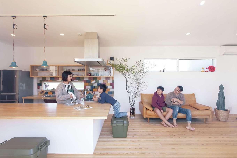 ソラマド静岡(オネストホーム)【デザイン住宅、間取り、平屋】塗り壁と無垢床のLDKで存在感を示す、ダイニングテーブルを兼ねた大きなキッチンカウンター。色合いを確認しながらセレクトしたタイルが空間のアクセントに。