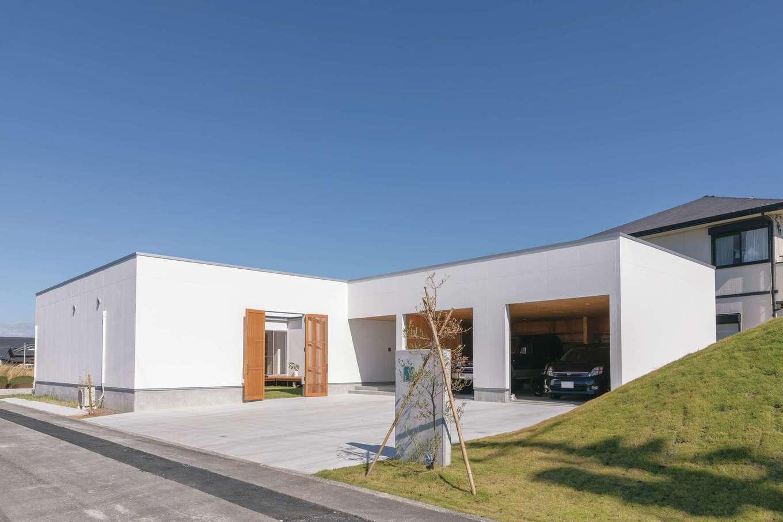 ソラマド静岡(オネストホーム)【デザイン住宅、間取り、平屋】車2台をゆったり収容できるガレージ付き。中庭との壁には直接行き来できる扉を。M邸のランドマークとしてそびえる緑の小山は、整地の際にでた残土で作ったもの。遊び心がうかがえる