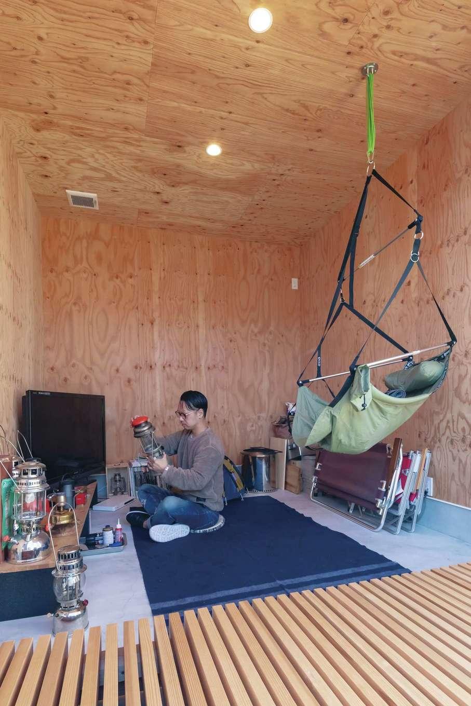 ソラマド静岡(オネストホーム)【デザイン住宅、間取り、平屋】アウトドアグッズをそのままインテリアにした趣味部屋。土間や下地材の壁で男前な印象に仕上げている。家族共有のスペースなので、子どもたちがここでテレビやDVDを観ることも