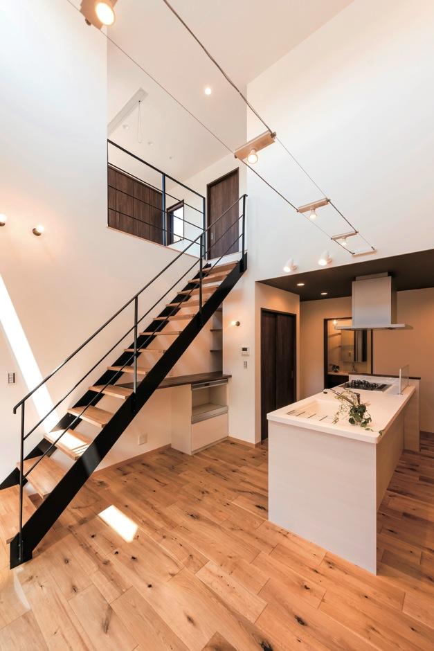 ホームプラザ大東【デザイン住宅、趣味、ガレージ】ダイニングは開放的な吹き抜け。ワイヤーで渡すタイプのダウンライトも、空間をお洒落に演出している