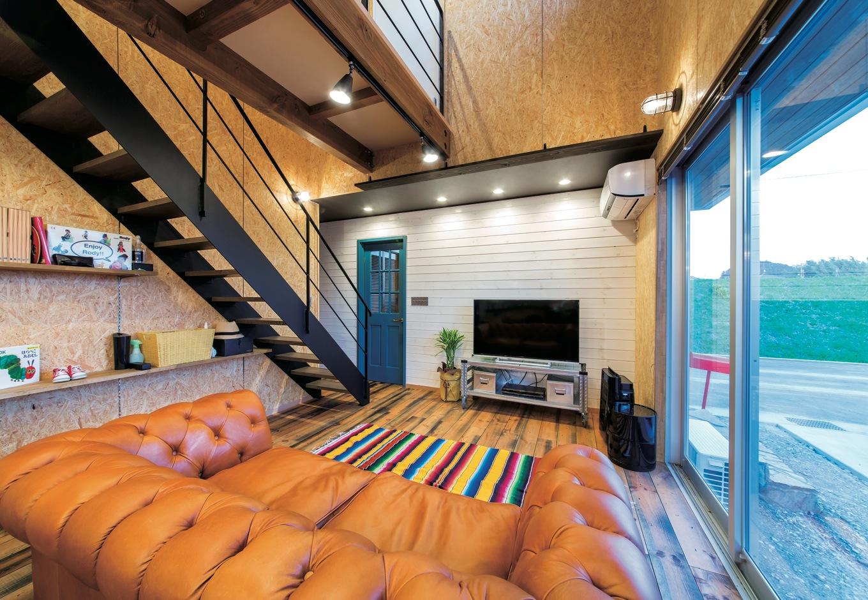 ホームプラザ大東【デザイン住宅、趣味、インテリア】スケルトン階段と2階の廊下がダイナミックに吹き抜けを渡る。階段下は可動棚のディスプレイスペースに