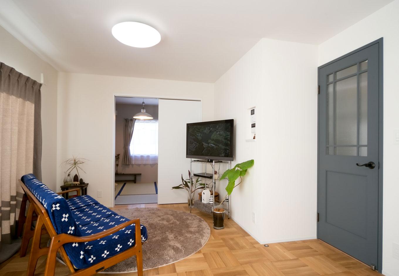 ホームプラザ大東|かわいいらしいブルーの扉が目を引くリビング。奥の和室も白を貴重とし、一体感を生んだ