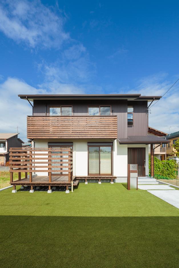 福工房【子育て、趣味、自然素材】青空と緑の芝生に映える、白と茶の外観。総2階は、構造的にも安定している