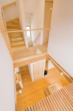 家の中央に設けられた吹き抜けが光と家族の気配を運ぶ。手すりには広さ、明るさが増えるよう強化ガラスを採用