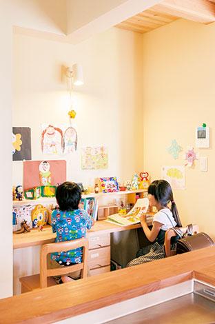 福工房【子育て、自然素材、間取り】リビングの一角に設けられたスタディコー ナー。キッチンのすぐ横なので、家事をしながら宿題を見たり、本読みを聞いたり。前の棚や壁は、大切な「作品」の展示スペースに