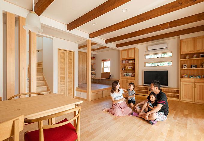ワイズホーム【デザイン住宅、子育て、収納力】ムクのぬくもりとデッキからの明るさに包まれたLDK。家族の団らんを中心に間取りが計画され、動線や収納、お子さんたちの成長による暮らし方の変化にも細やかな配慮が行き届く。天井の梁はLDKとキッズリビングで色を変え、穏やかに役割を分けている