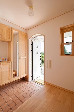 ワイズホーム【デザイン住宅、子育て、収納力】収納、鏡、カウンターと、必要なものを必要なサイズで用意。それらを明るい色調でまとめ、限られたスペースながら大らかさが漂う空間となった。上部がRになった玄関ドアは外観のアクセントにもなっている