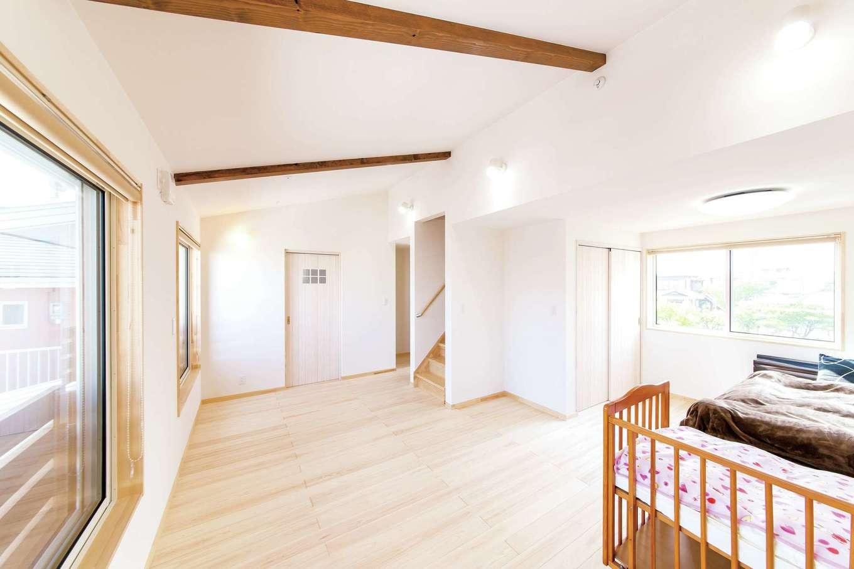 ワイズホーム【子育て、自然素材、省エネ】勾配天井を活かしたゆったり空間の2階ホール。今は家族3人の寝室に。将来は子ども部屋として仕切ることも可能